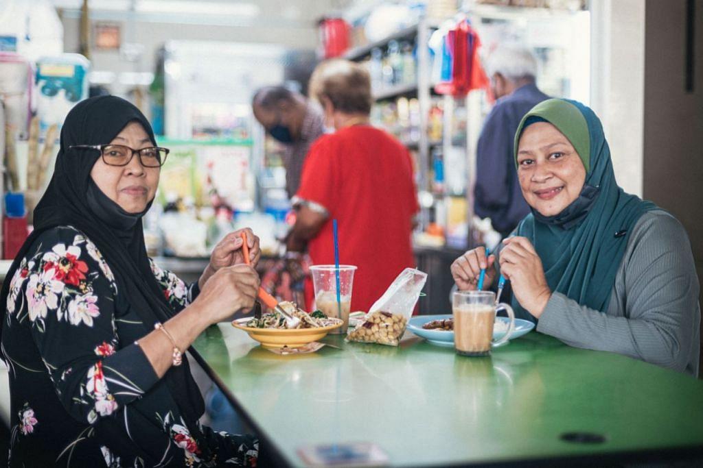 DAPAT SARAPAN BERSAMA: Cik Norimah Ngaji (kiri), dan adiknya Cik Norsimah Ngaji, bersarapan bersama di pusat penjaja di Pusat Pertukaran Bas Bedok semalam apabila larangan makan di luar dilonggarkan kepada kumpulan hanya dua orang yang diizin menjamu selera di luar. - Foto BH oleh HARITH MUSTAFFA