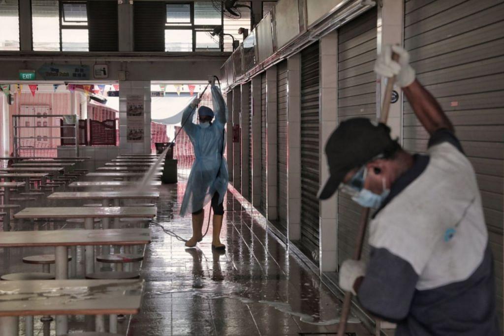 KERJA PEMBERSIHAN DIJALANKAN: Para pekerja sedang melakukan kerja pembersihan dan pembasmian kuman di Pusat Makanan dan Pasar Haig Road yang ditutup hingga 4 Ogos. - Foto BH oleh KEVIN LIM .