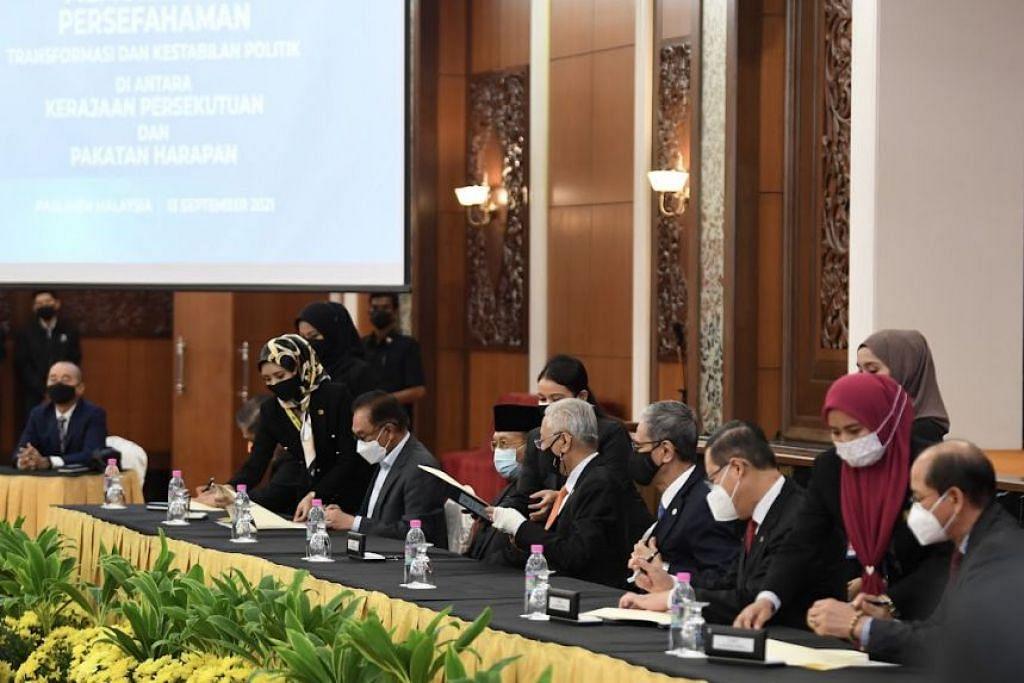 Perdana Menteri Malaysia, Ismail Sabri Yaakob (duduk, keempat dari kanan) menandatangani perjanjian kerjasama dengan Pakatan Harapan pada 13 September 2021. - Foto PEJABAT PERDANA MENTERI, MALAYSIA
