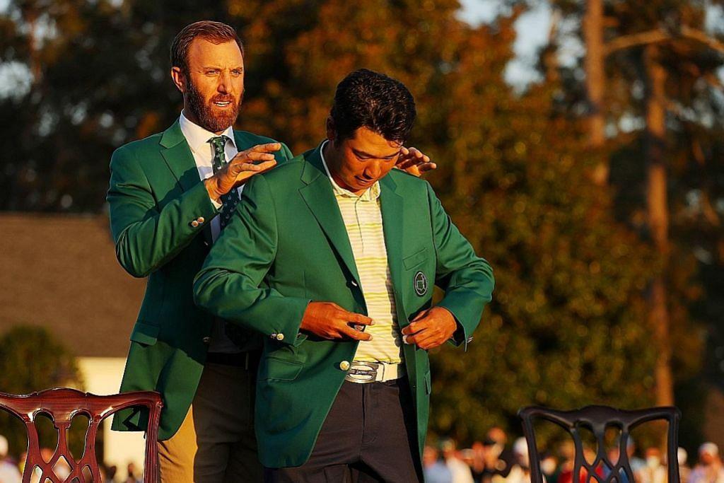 BANGGA: Matsuyama (depan) dibantu memakai 'jaket hijau' bagi juara oleh pemenang di Augusta tahun lalu, Dustin Johnson. - Foto AFP